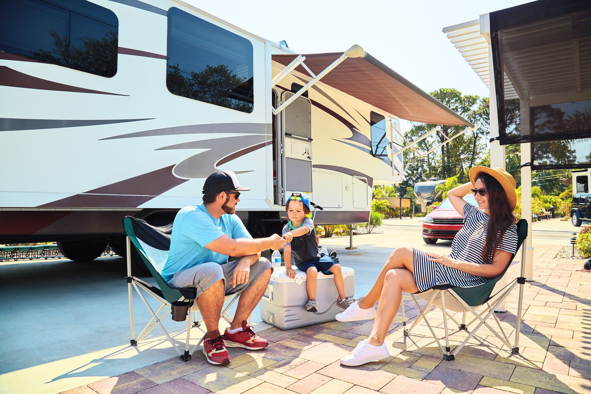Mother,,Father,And,Son,Sitting,Near,Camping,Trailer,smiling.woman,,Men,,Kid
